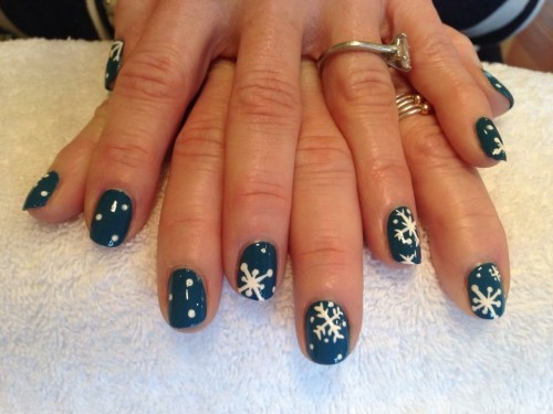 photo of two hands with decorative snowflake nail polish